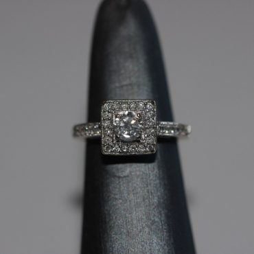 Beautiful 14 k white gold ring with a square design of multiple shimmering diamonds accenting one bright diamond in the center.